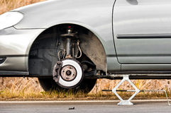 Car without tire on the road Royalty Free Stock Photo