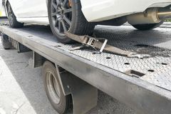 Car tire secured with safety belt on flatbed tow truck Royalty Free Stock Photography