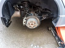 The car is at the tire shop. Under the jack the car in car-care center. The car with the removed wheel. The car is at the tire shop. Under the jack the car in stock photography
