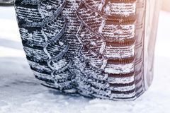 The car tire in the snow close up. Car tracks on the snow. Traces of the car in the snow. Winter tires. Tyres covered with snow at royalty free stock photography