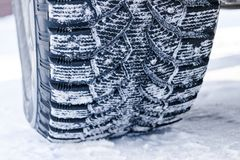The car tire in the snow close up. Car tracks on the snow. Traces of the car in the snow. Winter tires. Tyres covered with snow at stock photography