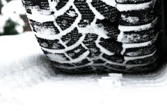 The car tire in the snow close up. Car tracks on the snow. Traces of the car in the snow. Winter tires. Tyres covered with snow at. Winter road royalty free stock photography
