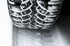 The car tire in the snow close up. Car tracks on the snow. Traces of the car in the snow. Winter tires. Tyres covered with snow at. Winter road stock photography