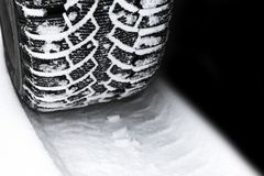 The car tire in the snow close up. Car tracks on the snow. Traces of the car in the snow. Winter tires. Tyres covered with snow at. Winter road royalty free stock images