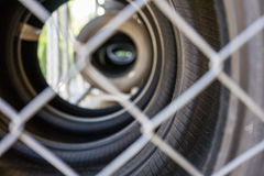 Car tire stack seen through fence. Close up Royalty Free Stock Photos
