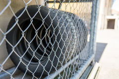 Car tire stack seen through fence. Close up Stock Images