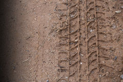 A car tire trace on dark red laterite. Shown deep mark of the car tire. royalty free stock image