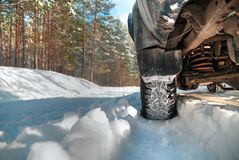 Car tire on winter forest. Road covered with snow stock photo