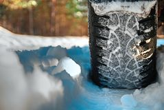 Car tire on winter forest. Road covered with snow. Close-up royalty free stock images