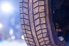 Car tire in winter on the road covered with snow closeup.  royalty free stock photo
