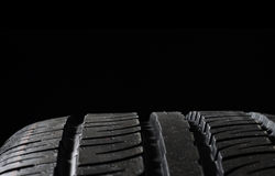 Car tires close-up. Winter wheel profile structure on black background Royalty Free Stock Photography