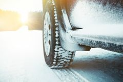 Car tires covered with snow on winter road through forest. Stock Photography