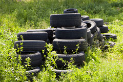 Car tires pollute the environment. Used tires thrown in nature Stock Image