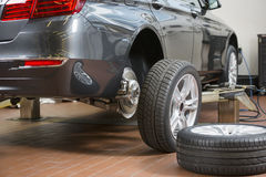 Car and tires at repair shop Royalty Free Stock Photo