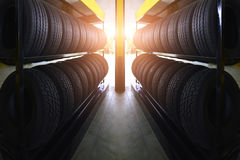 Car tires at warehouse with sun rays. Car tires for sale at a tire store Royalty Free Stock Photography