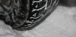 Car tires on winter road covered with snow stock image