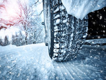 Car tires on winter road. Covered with snow. Vehicle on snowy alley in the morning at snowfall royalty free stock images