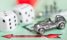Car token on a monopoly game board Stock Images