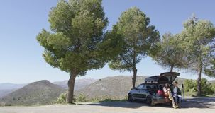 Car with tourists on mountain road. Tourists sitting in car trunk near road under trees with view of mountains on background stock video footage