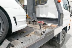 Car towed onto flatbed tow truck with hook and chain. Broken down auto vehicle car towed onto flatbed tow truck with hook and chain stock photography