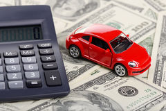 Car toy and calculator stay on the dollars Stock Photos