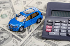 Car toy and calculator stay through the dollars. (Installation on the theme of car purchasing and auto credit Royalty Free Stock Photography