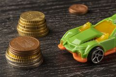 Car toy and euro coins on a dark wooden background stock photography