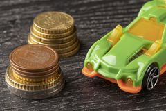 Car toy and euro coins on a dark wooden background stock photo