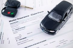 Car toy and keys on insurance documents. Royalty Free Stock Photos