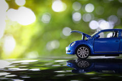 Car toy problem broken down parked with open hood of vehicle. Miniature car toy problem broken down parked with open hood of vehicle waiting for repair service Royalty Free Stock Images