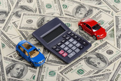 Car toys and calculator among the dollars. (Installation on the theme of car purchasing and auto credit Royalty Free Stock Photography
