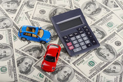 Car toys and calculator through dollars. (Installation on the thrme of car purchasing and credit Stock Photo