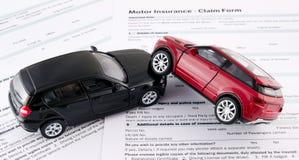 Car toys on motor insurance claim form. Motor insurance claim form. Car crash and protection concept Royalty Free Stock Photos
