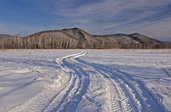 Car trace on a snow-covered field Royalty Free Stock Images