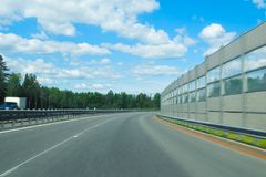 Beautiful landscape on the background of the transport road. Car track photographed while driving. Bright clouds and green trees highlight the beauty and royalty free stock photography