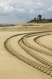 Car tracks in the sand. Severar car tracks in the sand with windmills on the background Royalty Free Stock Image