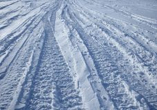 Car tracks in the snow. Winter road: vehicle tracks crossing the winter terrain royalty free stock image