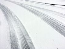 Car Tracks on a Snow Covered Road Stock Image
