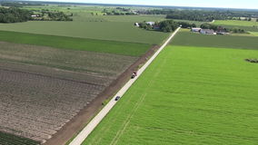 Car and tractor passing on a small countryside road stock footage