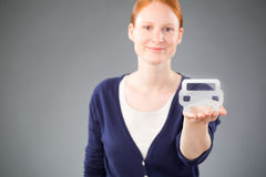 Car Trade and Insurance Concept. A young Caucasian woman holding a virtual vehicle in her hand, offering to insure or sell it Royalty Free Stock Images