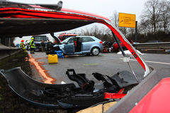 Car traffic accident III. Car crash with a red car in foreground and second car in background with fire fighters and police royalty free stock photos