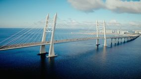 Car traffic on cable stayed bridge with view on urban infrastructure in developed cit. Beautiful landscape from flying drone on car traffic on modern cable stock video footage