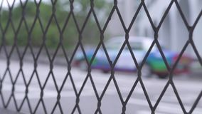 Car traffic on city road through fence mesh. View through wire fence mesh on car and taxi driving on urban highway in. Modern city stock video