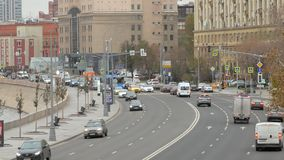 Car traffic on crossroad in big city in autumn day, embankment
