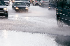 Car traffic driving on flooded city road during rush hours in ra Royalty Free Stock Image