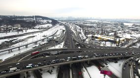Car traffic on highway junction in winter city. Aerial view winter crossroad
