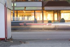 Car Traffic at night. Cars passing in front of shop displays at night Stock Photos