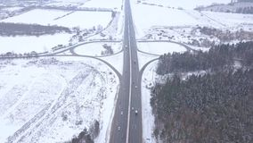 Car traffic on road junction at winter highway aerial view. Cars driving on crossroads and road intersection in snow highway drone view stock video