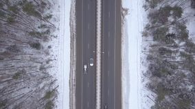 Car traffic on winter highway aerial view. Cars and truck driving on winter road. Car traffic on winter highway aerial view. Cars and cargo truck driving on stock footage