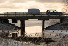 Car with a trailer crossing a bridge over a freezing lake Royalty Free Stock Photography